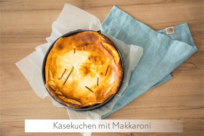 Ganzer Käsekuchen ohne Boden mit Makkaroni in der Creme auf einem Tuch.