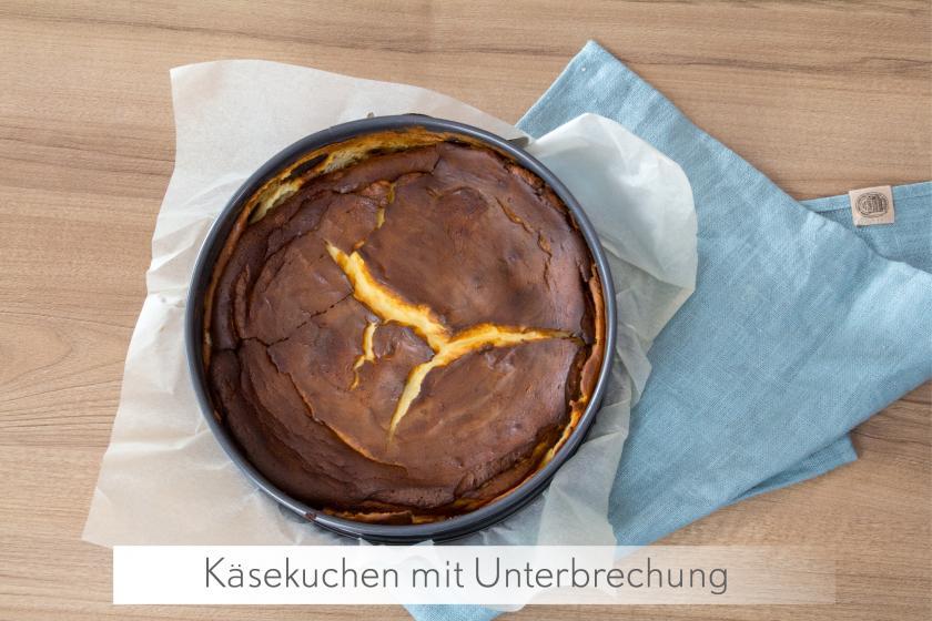 Ganzer Käsekuchen ohne Boden steht in der Form auf einem blauen Tuch.
