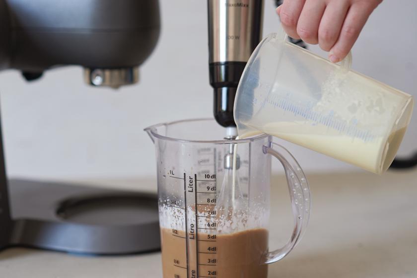 Sahne wird zu kaltem Kaffee in einem Messbecher gefüllt.