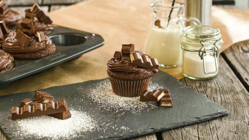 Kinderschokolade Cupcakes im Vordergrund mit weiteren Cupcakes im Hintergrund auf Schieferplatte.