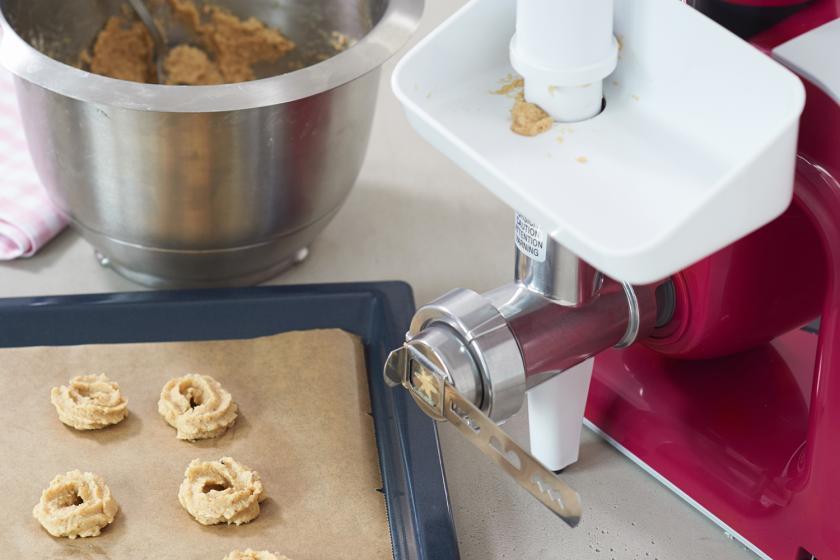 Kokos-Spritzgebäck wird mit einer Küchenmaschine in Form gebracht.
