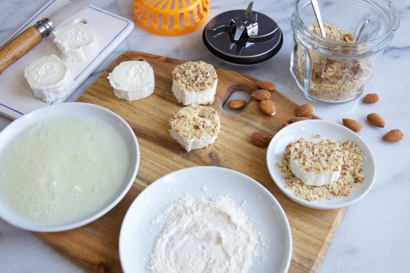 Zutaten für Kräutersalat in Tellern und Schalen auf Holzplatte.