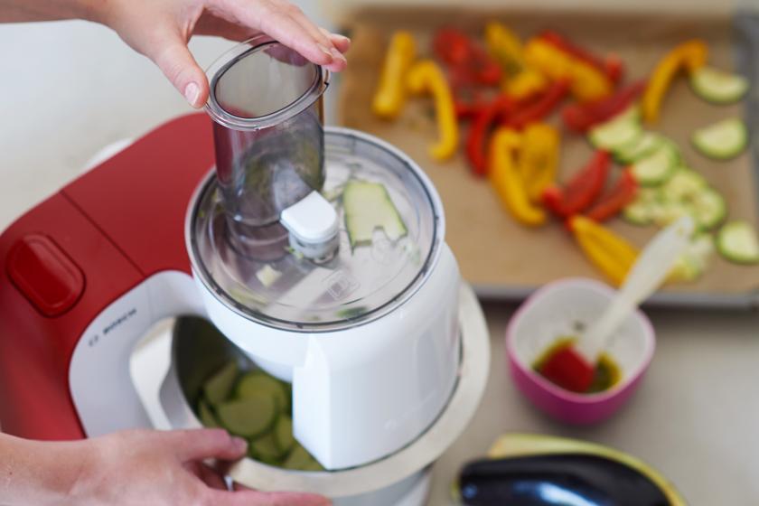 Für die Kräuterwaffeln mit Ratatouille wird Gemüse mit einer Küchenmaschine in Scheiben gehobelt.