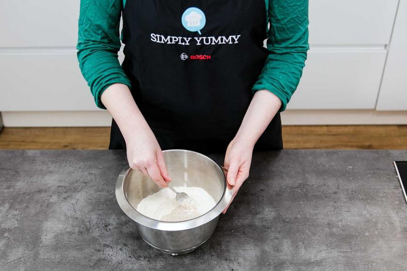 Es wird Mehl und Hefemilch in einer Schüssel zu einem Teig für Kreppel vermischt.