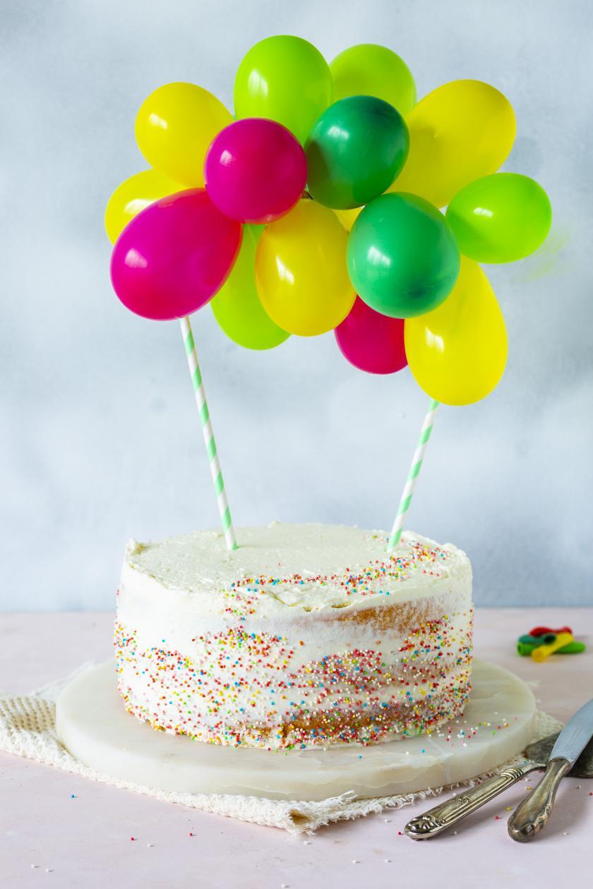 Torte mit Luftballongirlande auf einer Kuchenplatte.