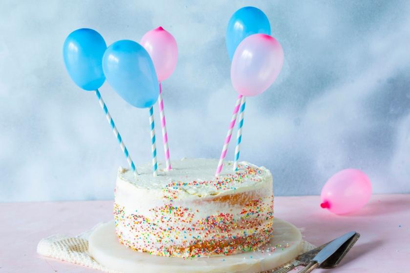 Luftballons an Strohhalmen in eine Torte gesteckt.