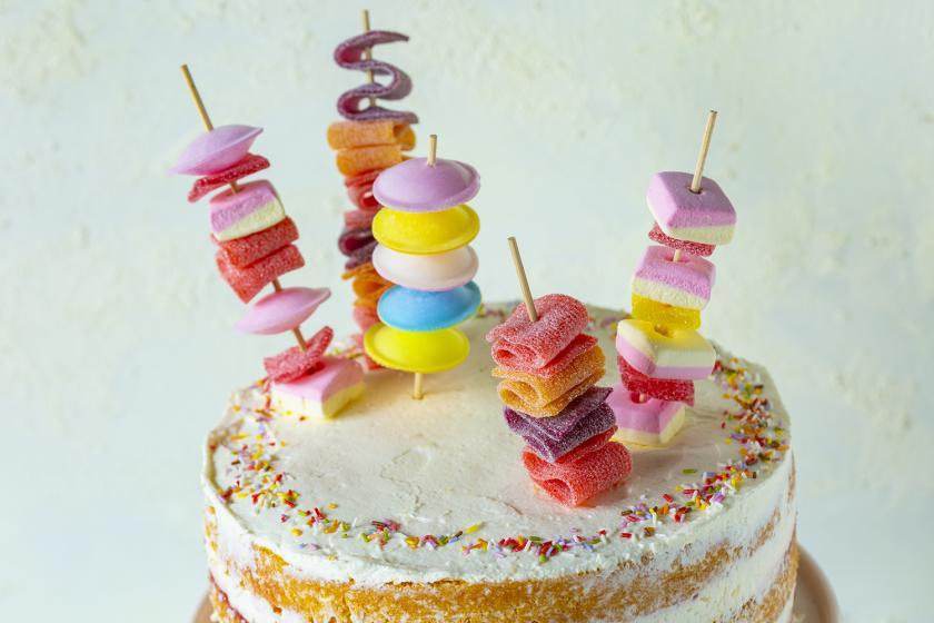 Mehrere Süßigkeitenspieße stecken in einer Torte.