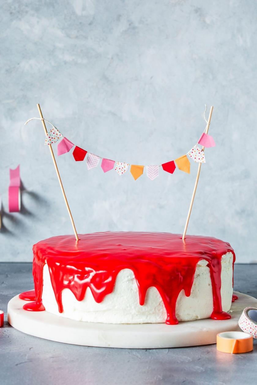 Torte mit Wimpelkette auf einer Kuchenplatte.