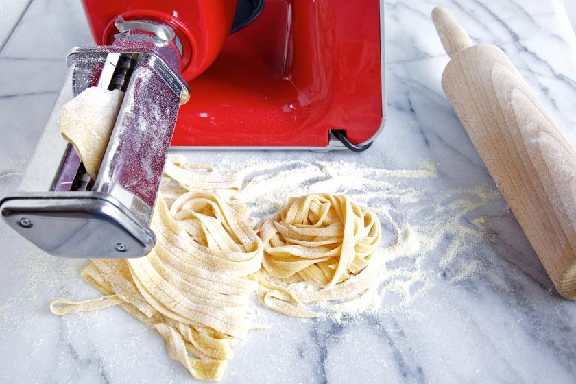 Der Teig vom Linguine Rezept wird mit einer Nudelmaschine in Streifen geformt.