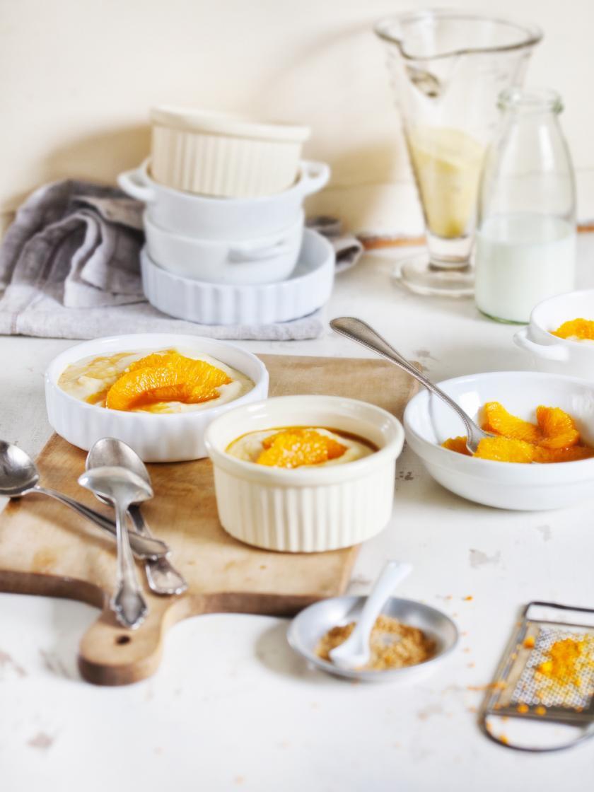 Marzipan-Grießbrei mit Orangenkompott in Schälchen auf einem Tisch angerichtet.