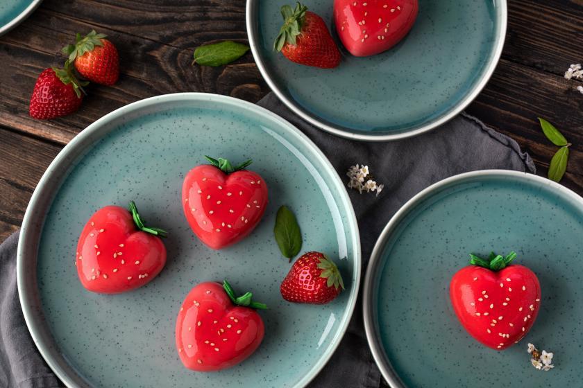 Kleine Mirror Glaze Erdbeertörtchen auf grauem Teller.