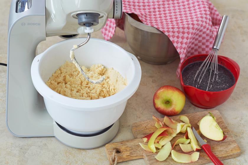 Teig, Apfel und Mohn in der Zubereitung für Mohnkuche mit Streusel.