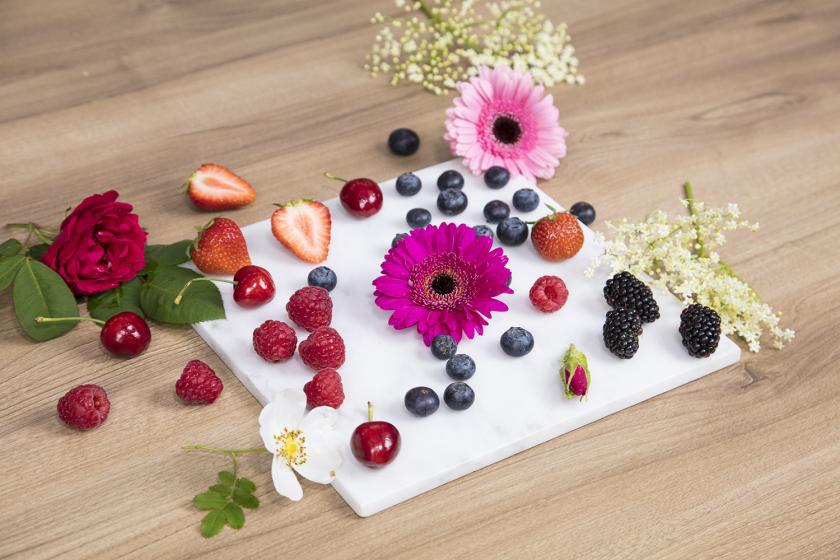 Verschiedene Beeren und Blumen für den Naked Cake liegen auf einer Platte verteilt.