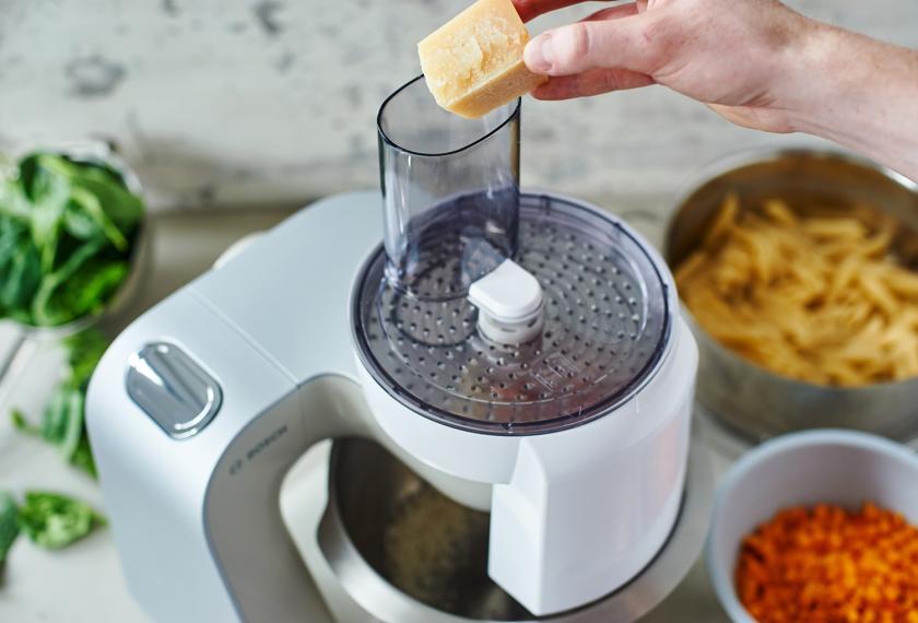 Für den Nudelauflauf mit Kürbis und Spinat wird Parmesan in einer Küchenmaschine gerieben.