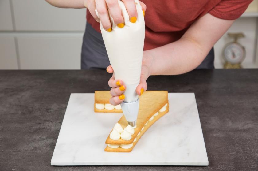 Mit einem Spritzbeutel  wird die Creme für den Number Cake verteilt.