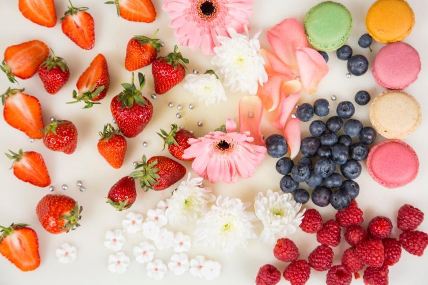 Verschiedene Beerenfrüchte, Blumen und Macarons auf weißem Untergrund.