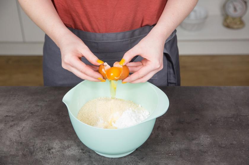 Ein Ei wird zu den restlichen Zutaten für den Number Cake in die Schüssel gegeben.