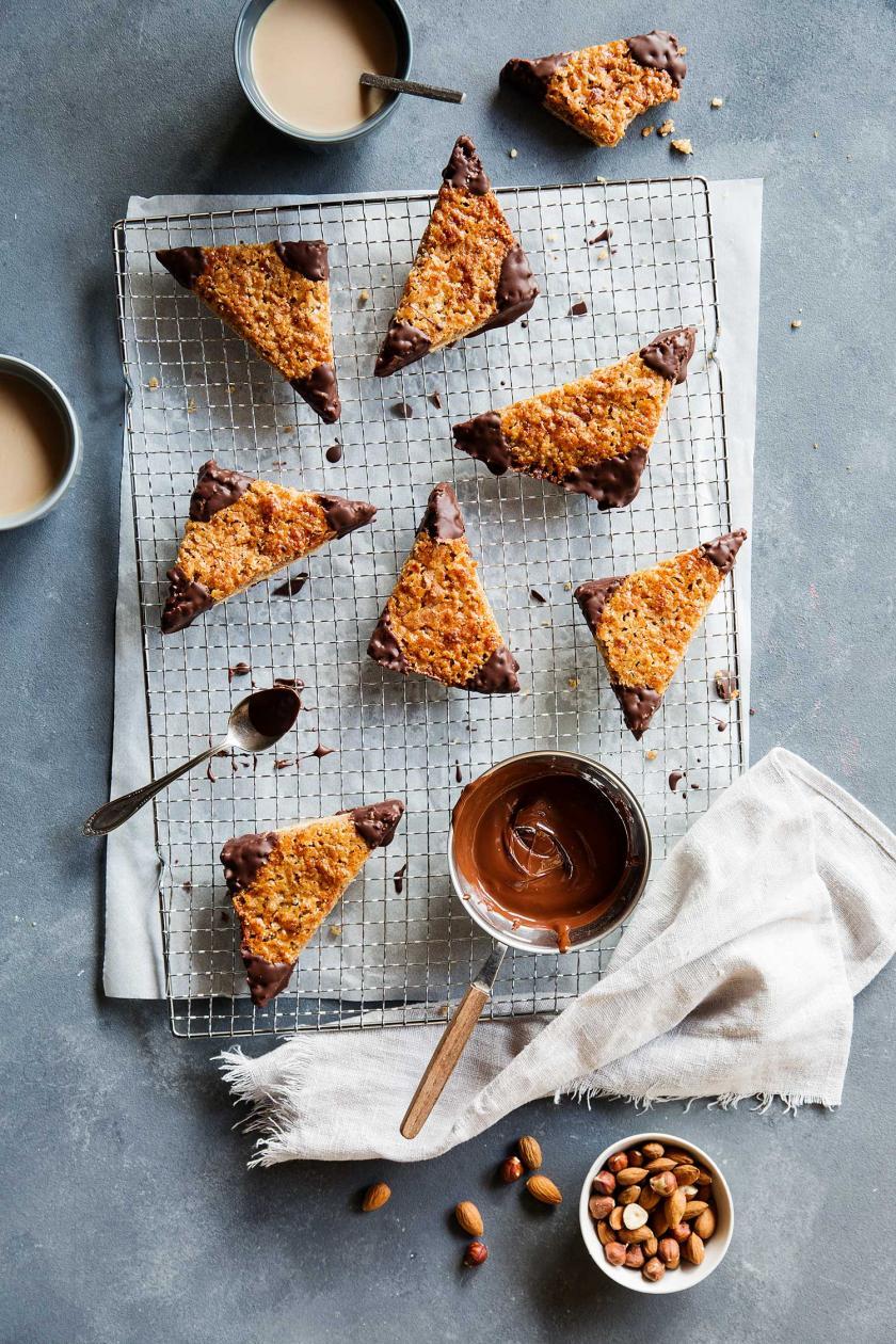 Sieben Nussecken auf Kuchengitter mit Schokolade und gemahlenen Nüssen.