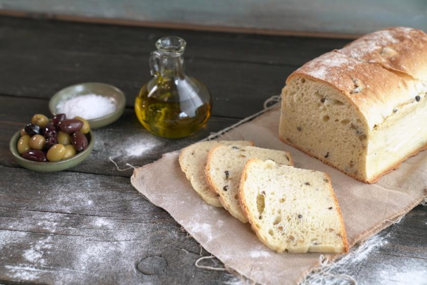 4 Scheiben Olivenbrot vor ganzem Olivenbrot mit Olivenöl und Oliven