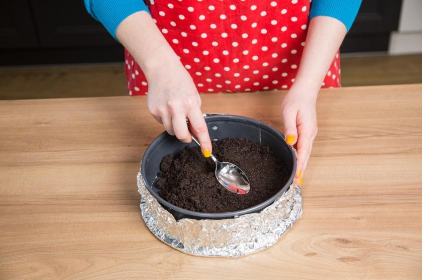 Die Keksmasse für den Oreo Cheesecake wird in der Springform festgedrückt.