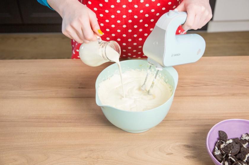 Zutaten für die Füllung des Oreo Cheesecakes werden mit einem Handmixer in einer Schüssel glatt gerührt.