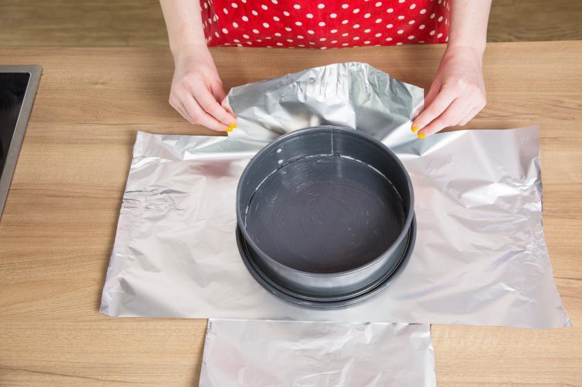 Die Springform für den Oreo Cheesecake wird mit Alufolie einschlagen.