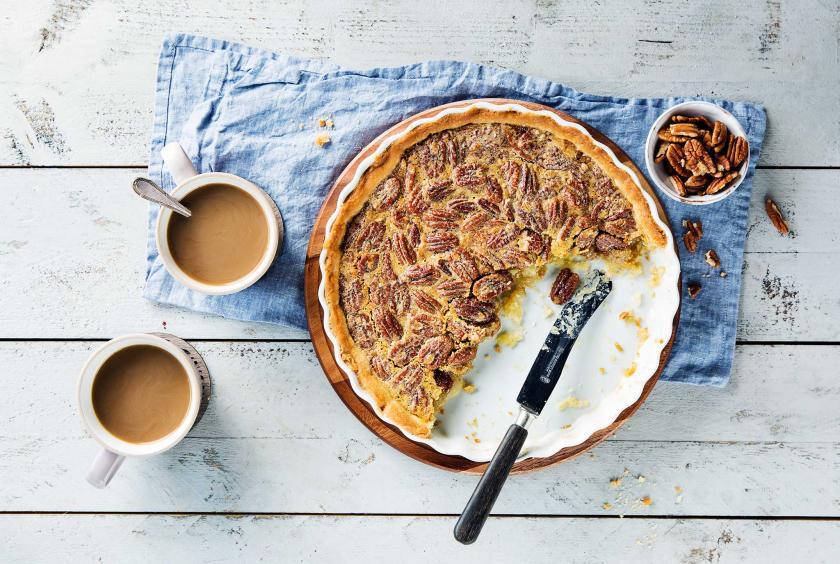Angeschnittener Pecan Pie in der Form. Daneben zwei Becher Kaffee.
