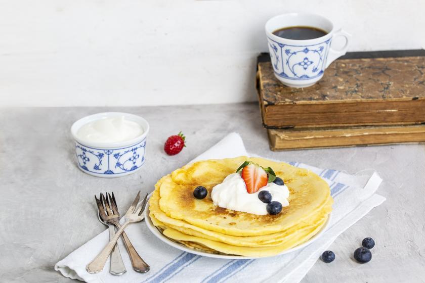 Pfannkuchen auf einem Teller mit Sahne und Blaubeeren.