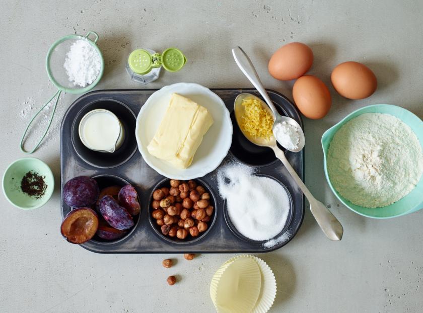 Zutaten für Pflaumenmuffins und Muffinblech nebeneinander