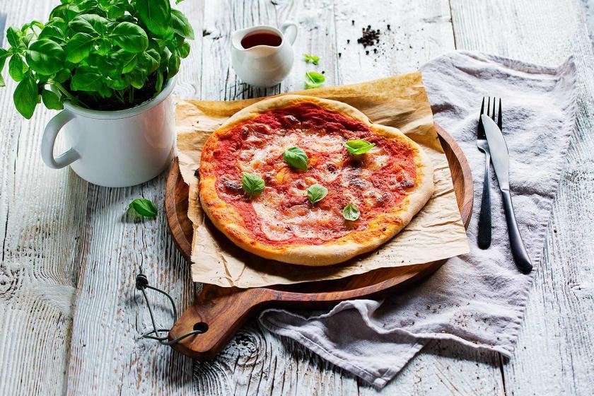 Pizza Margherita auf einem Stück Backpapier auf einem Holzbrett.