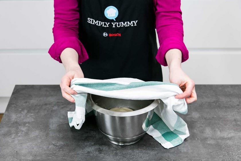 Der teig für Pizz margherita liegt in einer Schüssel, die mit einem Küchentuch abgedeckt wird.