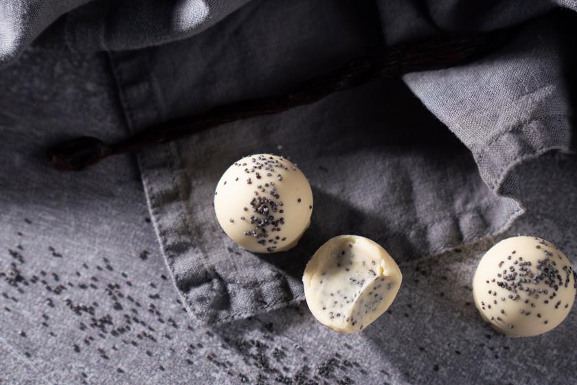 Drei selbst gemachte Pralinen auf einem grauen Tuch.