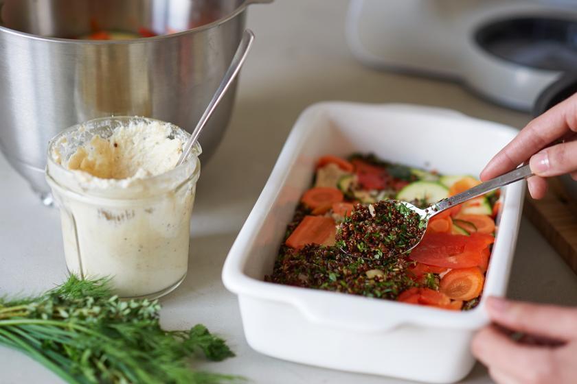 Quinoa-Auflauf wird mit Gemüse und Co. in einer Auflaufform geschichtet.