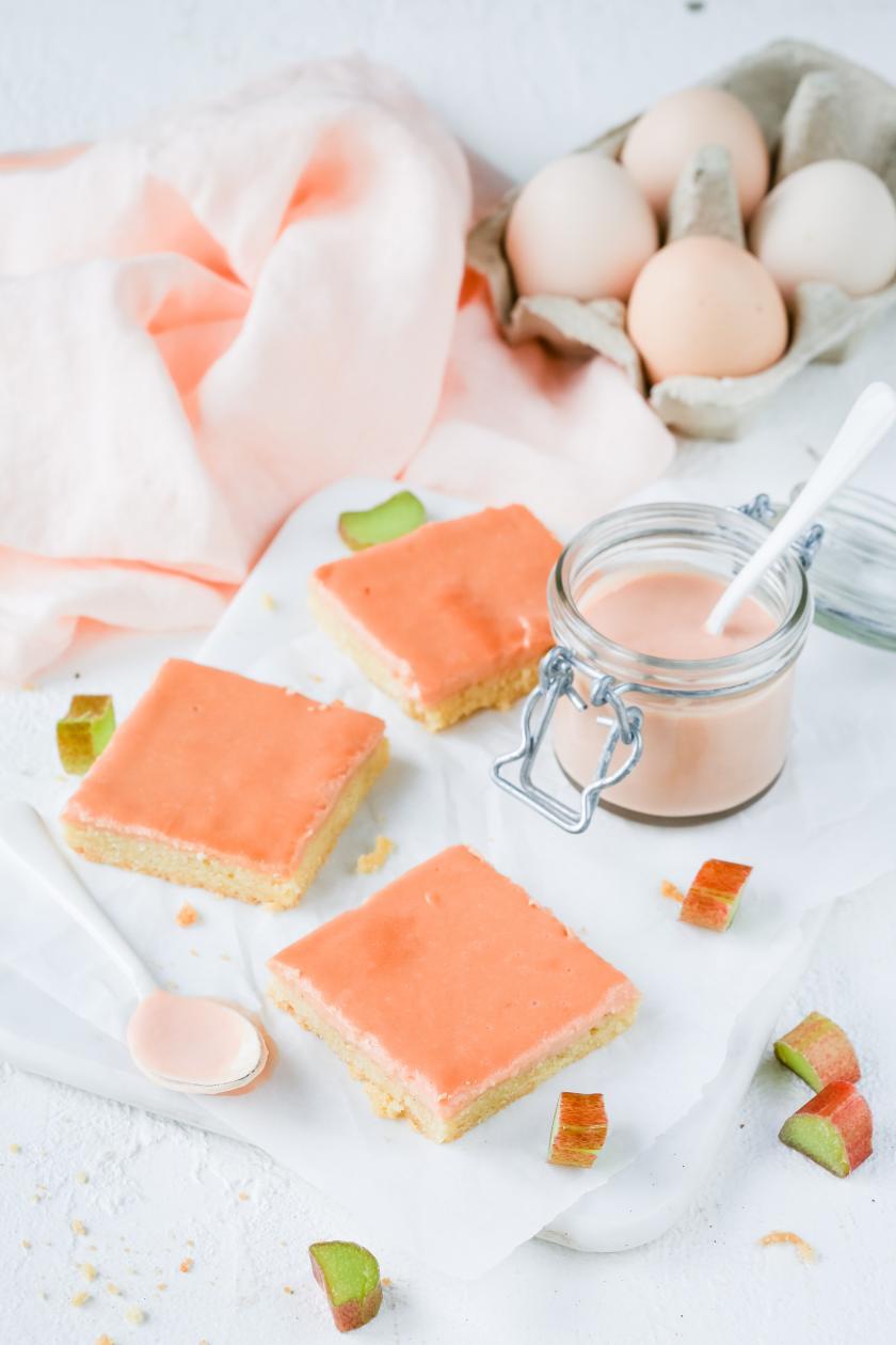 Mehrere Rhabarber-Curd-Schnittchen liegen auf einem Tisch. Drumherum Rhabarber Curd in einem Glas und Eier.