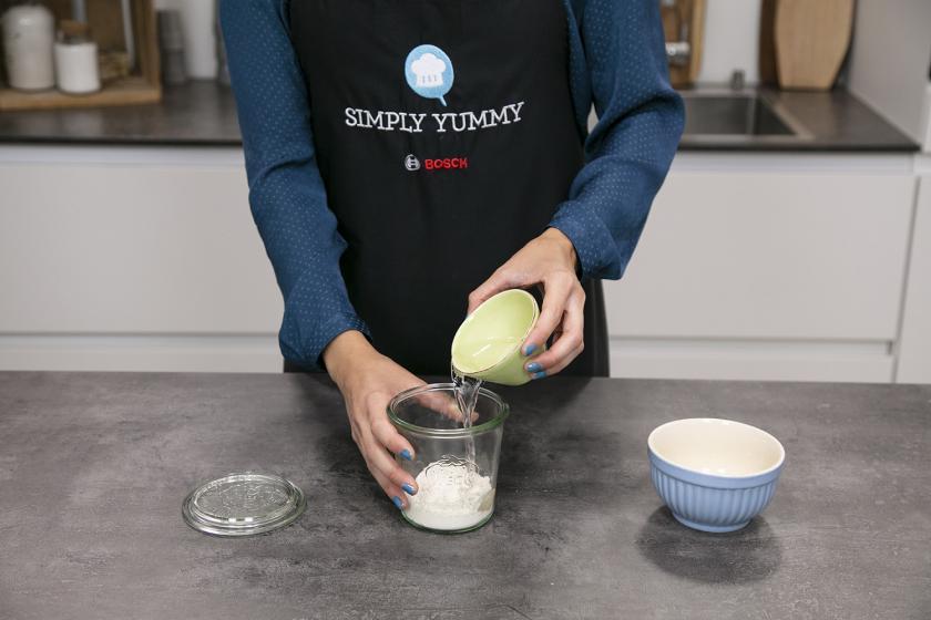 Für das Sauerteigbrot wird Wasser zu Mehl in ein Glas gegeben.