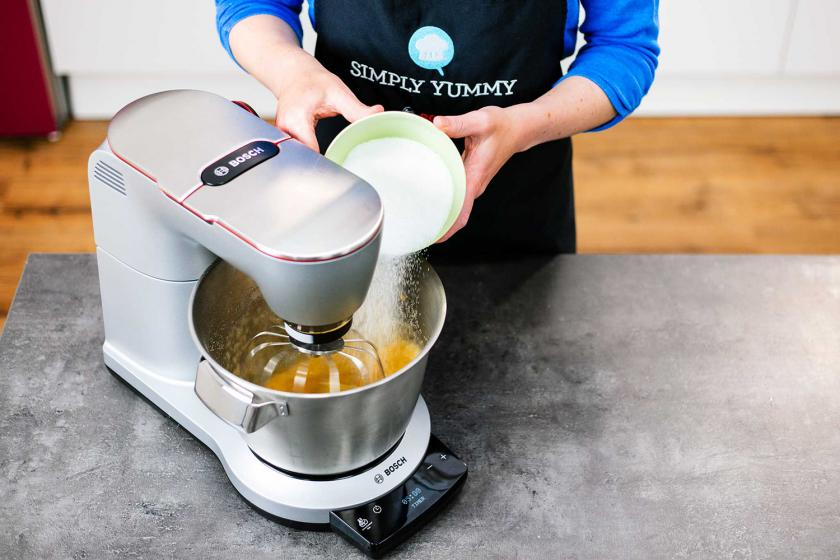 Für die Schneebälle wird Zucker in die Rührschüssel der Küchenmaschine gegeben.