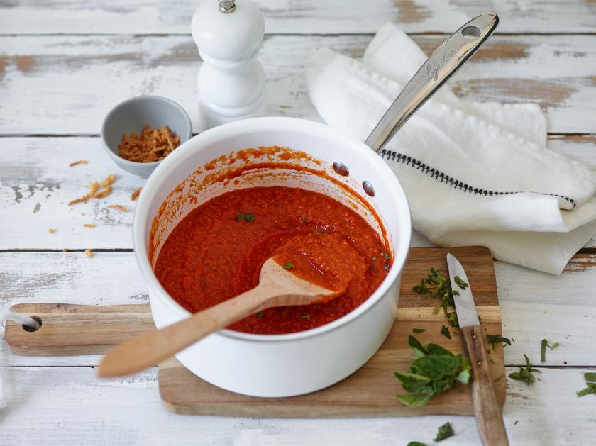 Schelle Tomatensoße ist einem Kochtopf mit Kochlöffel.