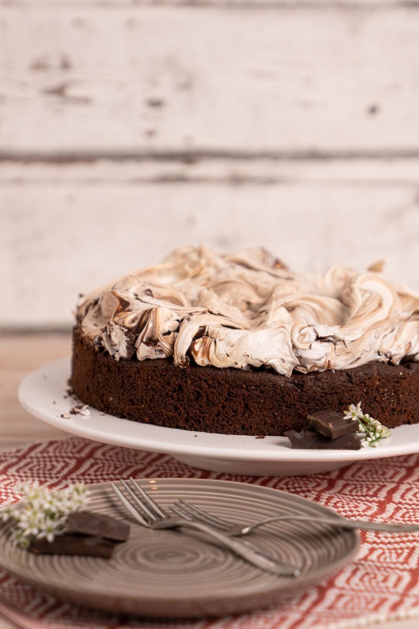 Angeschnittene Schoko-Baiser-Torte auf weißer Tortenplatte