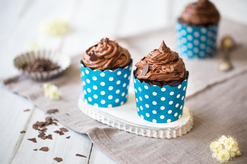 Zwei Schoko Cupcakes mit Frostig auf einem Tellereben. Im Hintergrund ein dritter Cupcake.
