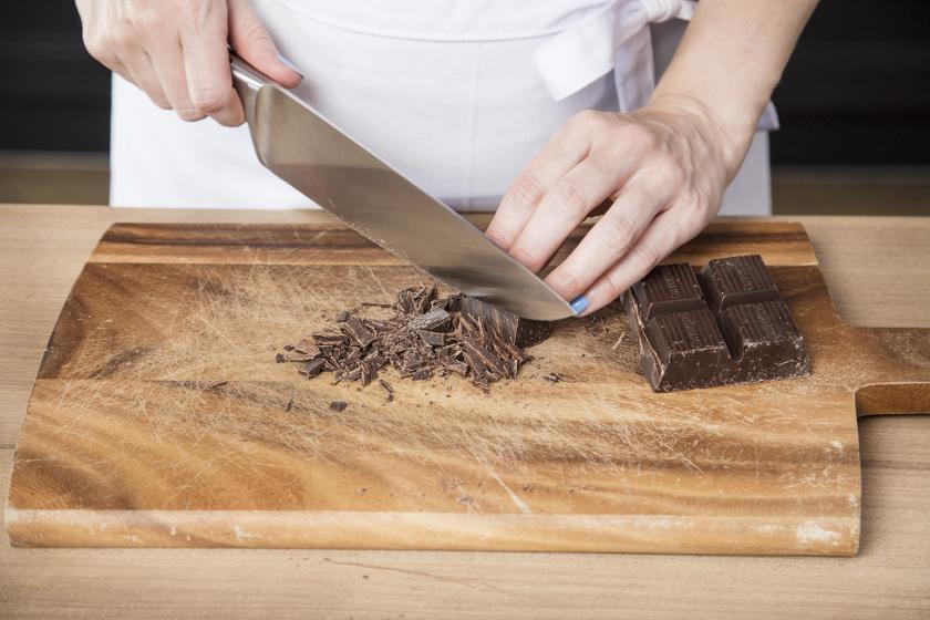 Für den Schoko-Kirsch-Kuchen wird Zartbitterschokolade gehackt.
