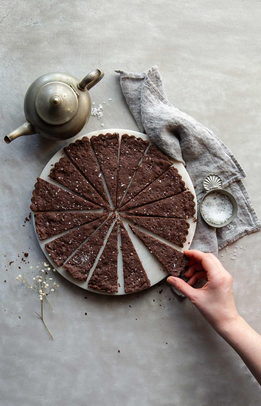 Schoko-Shortbread mit Meersalz in Stücken auf einem Teller, eine Hand greift danach.