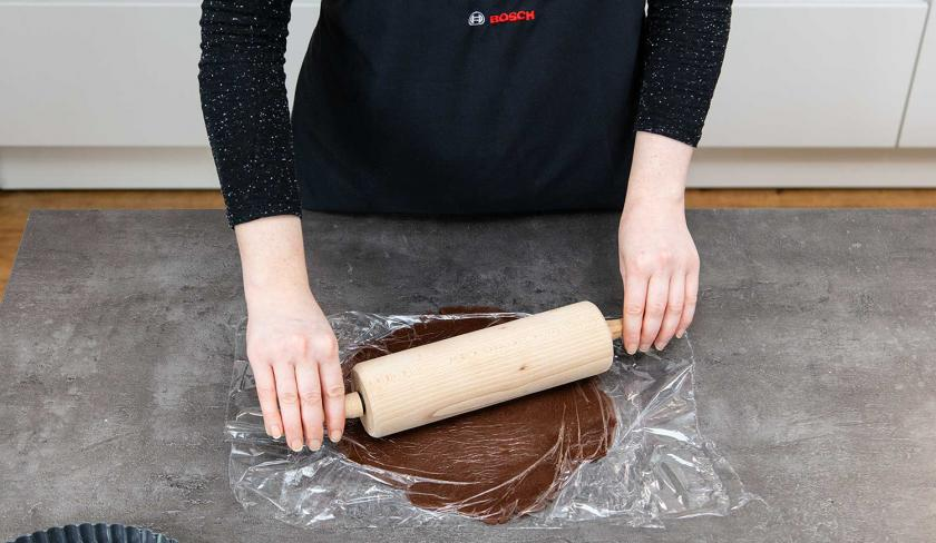 Der Teig für das Schoko-Shortbread wird zwischen zwei Stücken Folie ausgerollt.