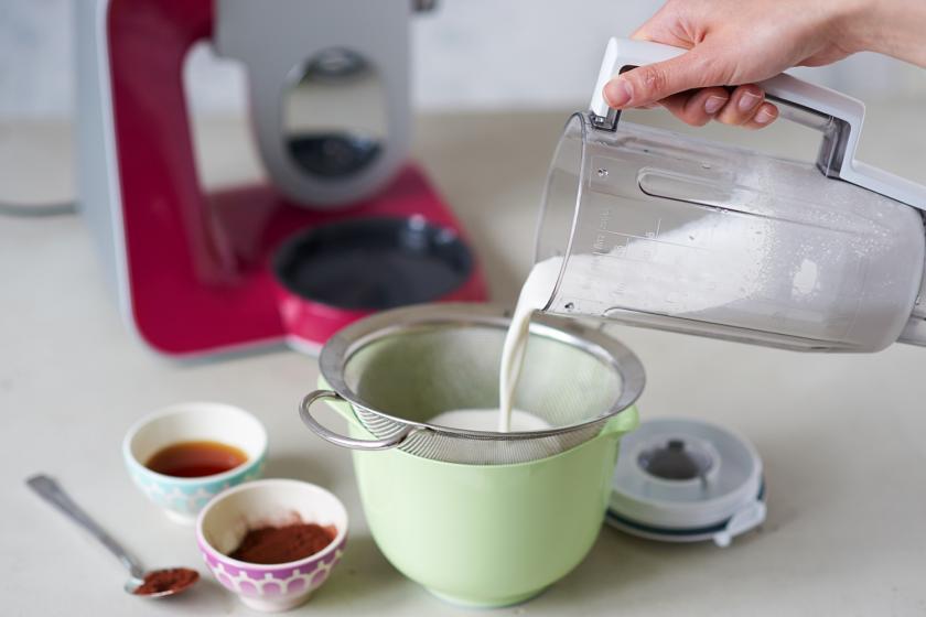 Mandelmilch für die Schoko-Mandelmilch wird durch ein Sieb gegossen.
