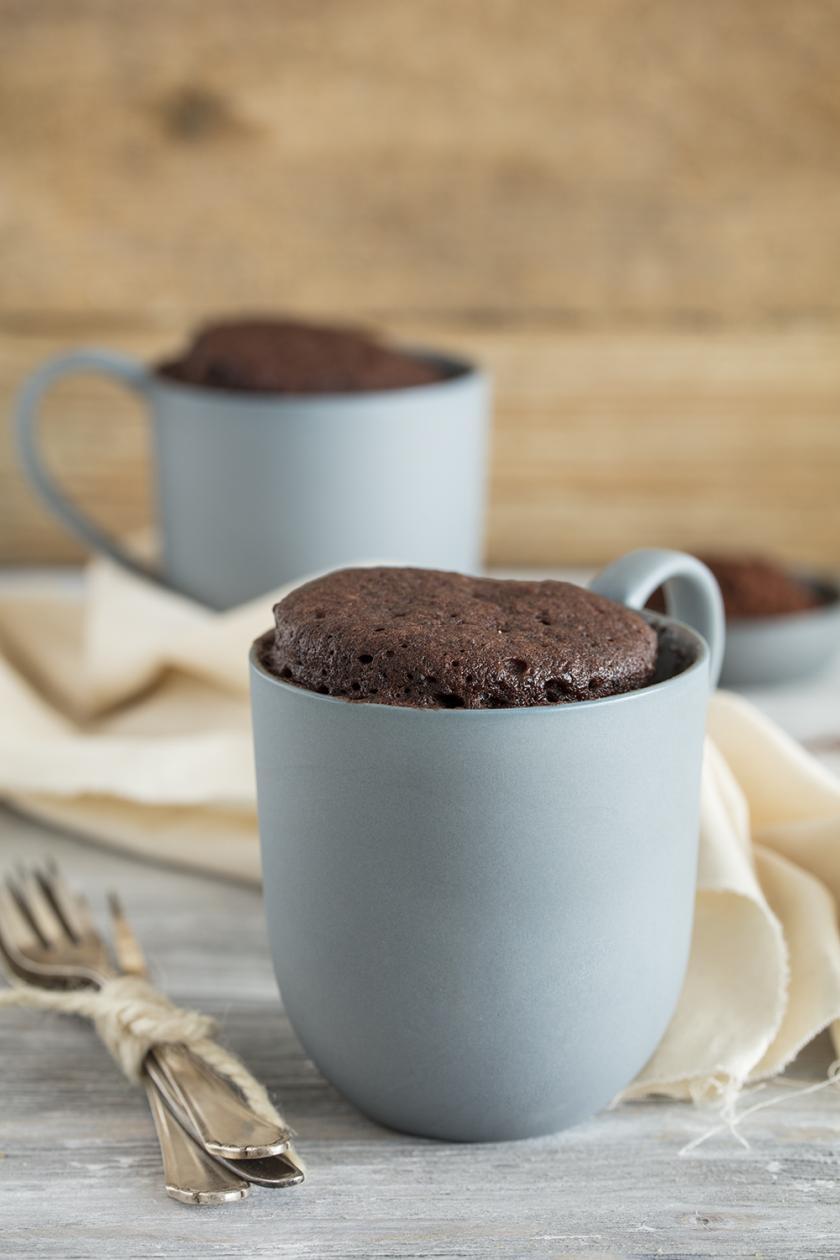 Ein Schoko Tassenkuchen steht auf einem grauen Holzuntergrund. Daneben liegt eine Kuchengabel.