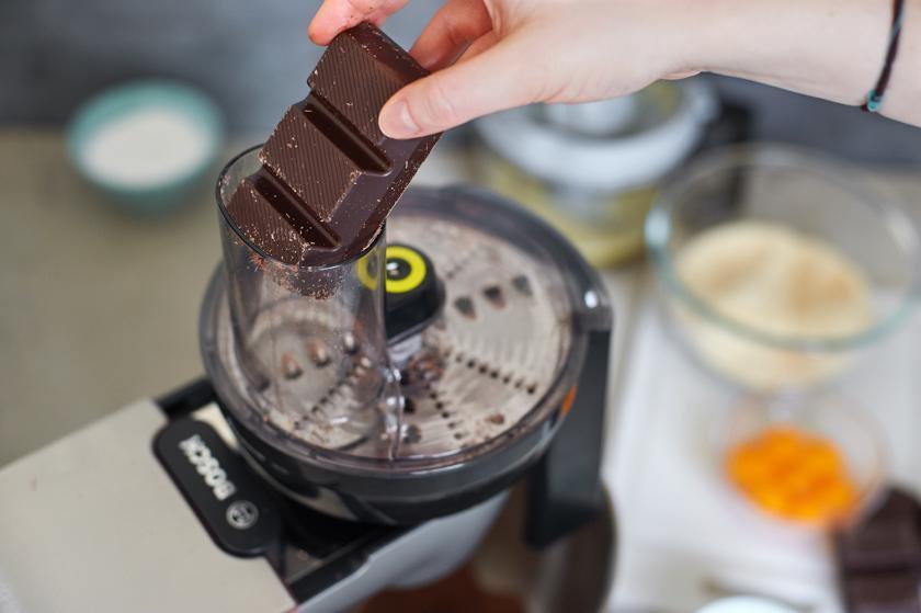 Zartbitterschokolade wird für den Orangen-Schoko-Kuchen gerieben.