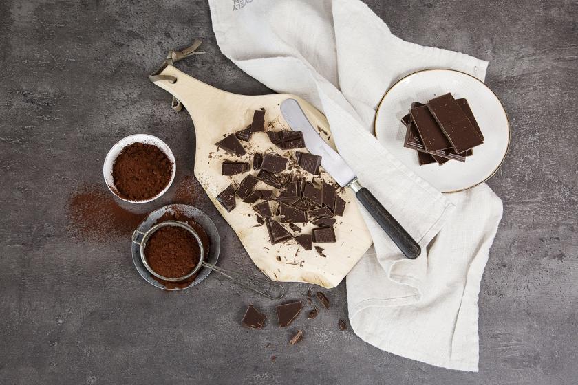 Kakaopulver, zerkleinerte Schokolade und Schokoladenstücke sind auf einem dunklen Untergrund drapiert.