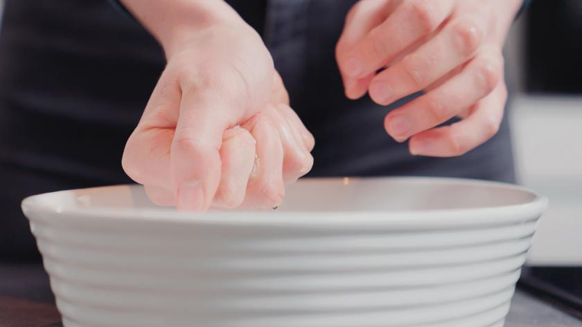 Für die Füllung der Schokomousse-Torte wird Gelatine in einer Hand ausgedrückt.