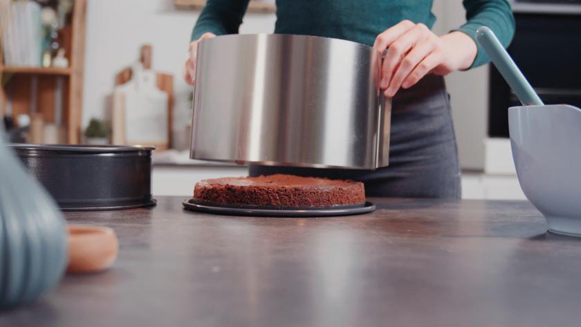 Ein Tortenring wird um den Boden der Schokomousse-Torte gesetzt.