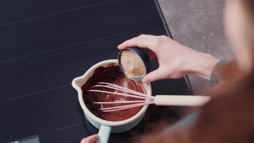 Zucker wird zu geschmolzener Schokolade in einen Topf mit angelehntem Schneebesen gegeben.