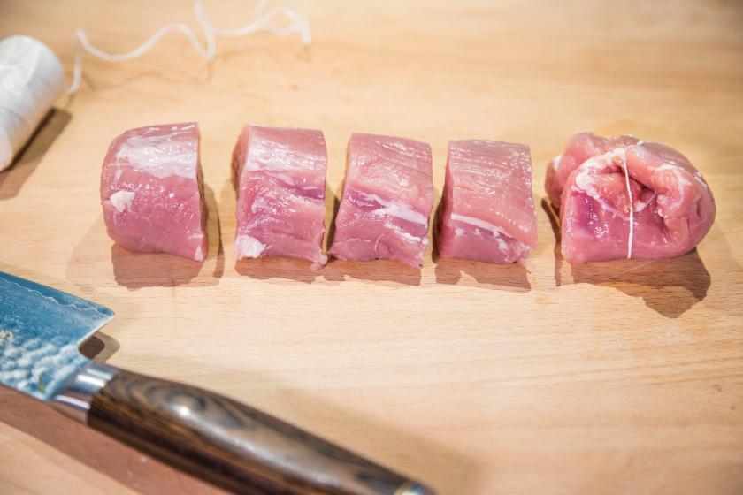 Fleisch liegt auf einem Brett und ist in Schweinemedaillons geschnitten.